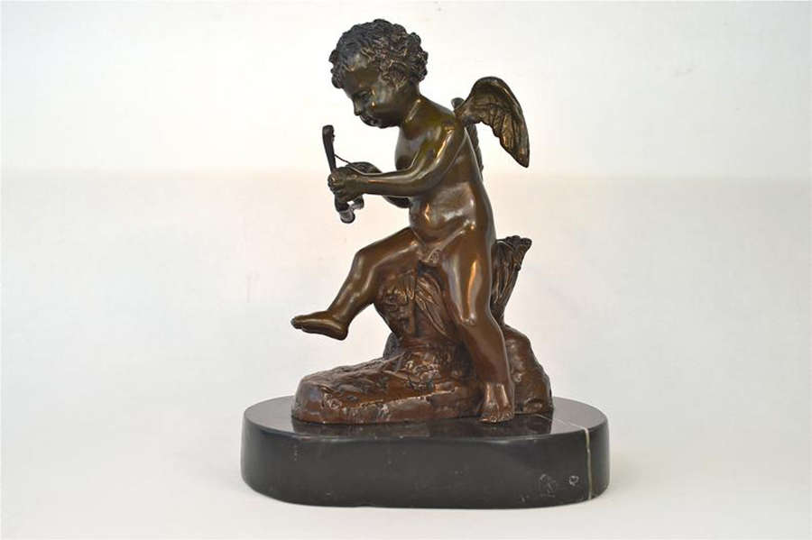 A beautiful seated Antique bronze cupid figure